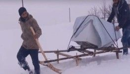 Arızalı bulaşık makinesi, karda kızakla taşındı