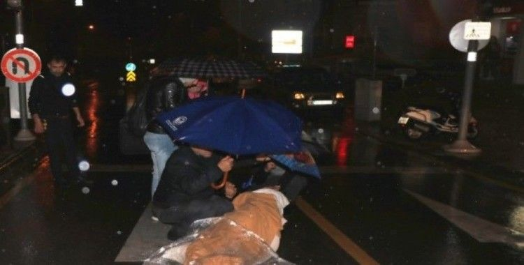 Motosikletten düşen kadını şemsiyelerle yağmurdan korudular