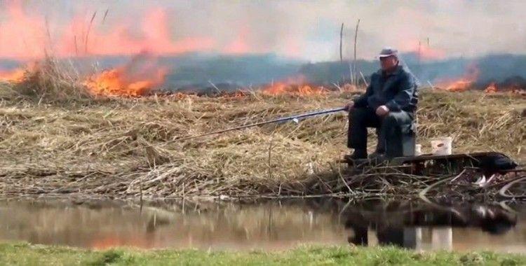 Yangına aldırmadan balık tutmaya devam etti